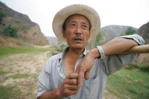 YANAN, CHINA:  A farmer holds onto his hoe while walking through a reforested valley sustaining crop growth in the compact yellow earth, known as loess, 26 May 2005, on the outskirts of Yan'an in western China's Shaanxi province, where World Bank loan projects help rehabilitate the loess plateau and the local population with growing crops in an otherwise and once desolate landscape.  China's ambitious western development program, launched in 1999, is for a vast region covering 12 provinces, municipalities and autonomous regions and home to nearly 30 percent of the country's total population left behind in economic development. The living standard of farmers in the Chinese countryside has witnessed a transition from a meager existence to a better-off life since economic reforms began over twenty years ago.  AFP PHOTO/Frederic J. BROWN  (Photo credit should read FREDERIC J. BROWN/AFP/Getty Images)